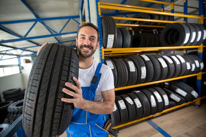 Reifen für Geschäftskunden - Pneu Schaller - Lachender Mechaniker mit Reifen